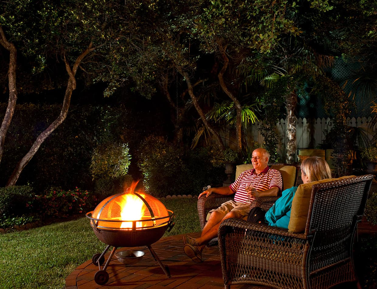 older couple relaxing by the fire pit at night