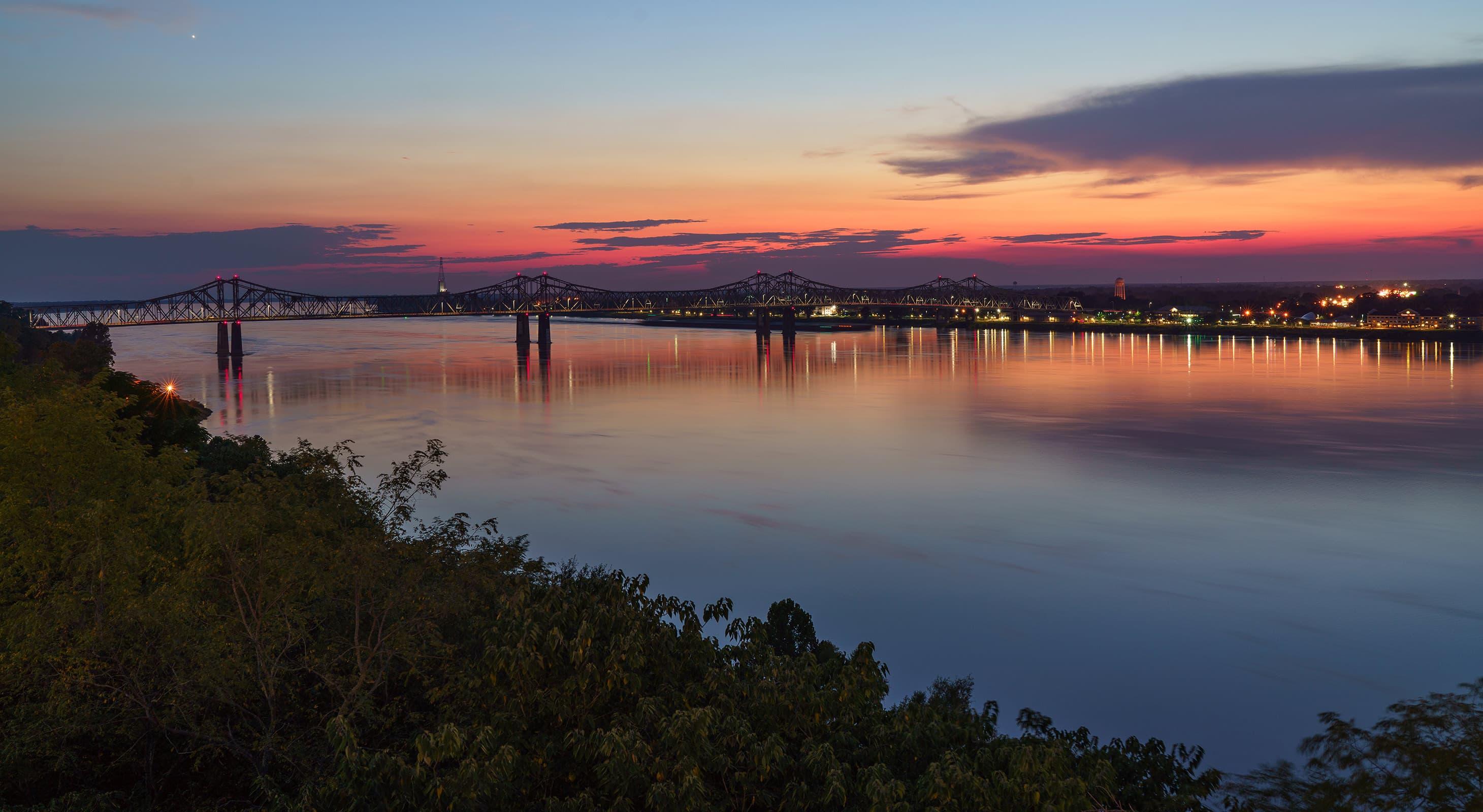bridge over river at sunset