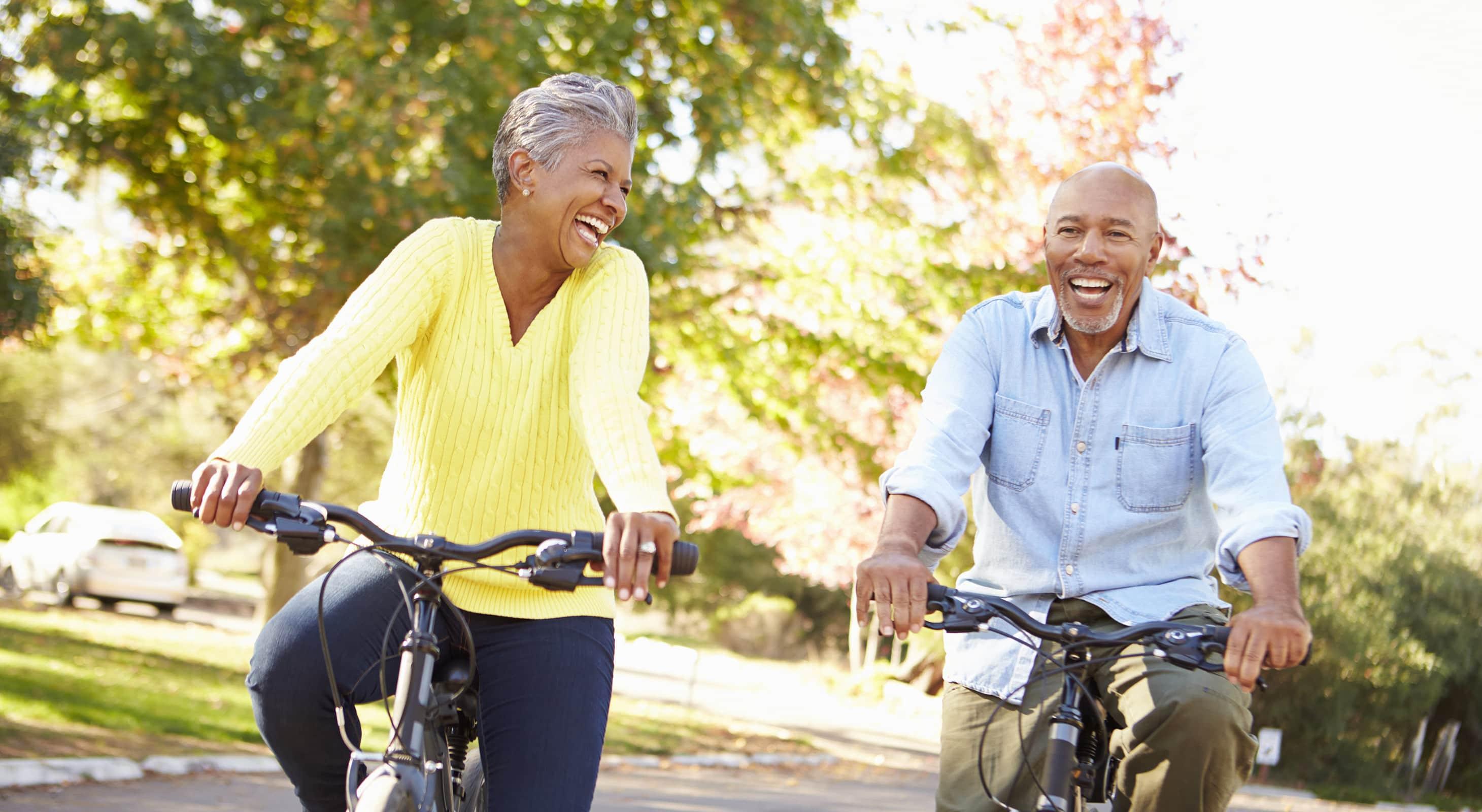 happy older couple riding bikes