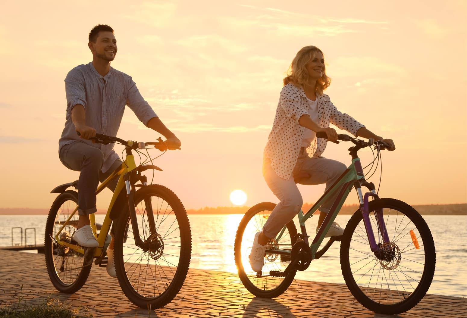 romantic couple biking at sunset